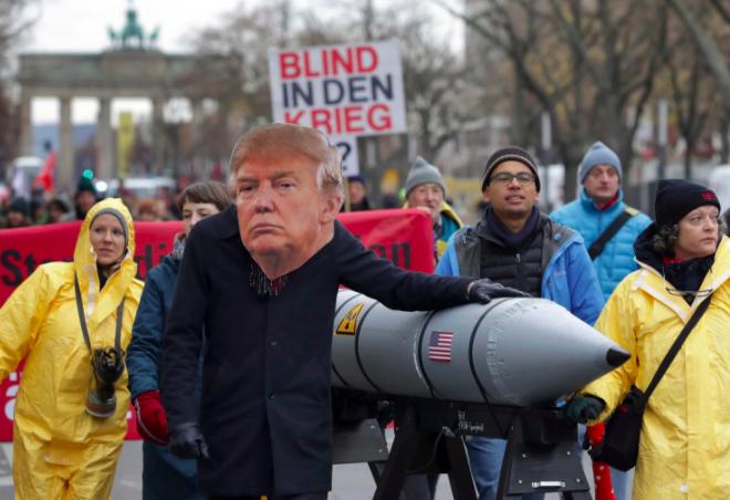 An anti-war protester wears a mask showing US President Donald Trump in Berlin, Germany, Saturday, Nov. 18, 2017 during a demonstration against nuclear weapons near the Brandenburg Gate. (Michael Sohn/Associated Press)