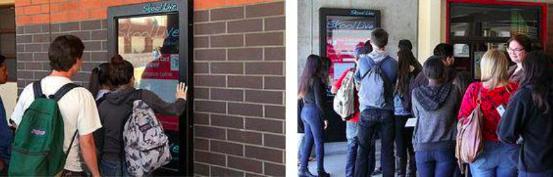 High school students line up to upload information onto the giant screens.