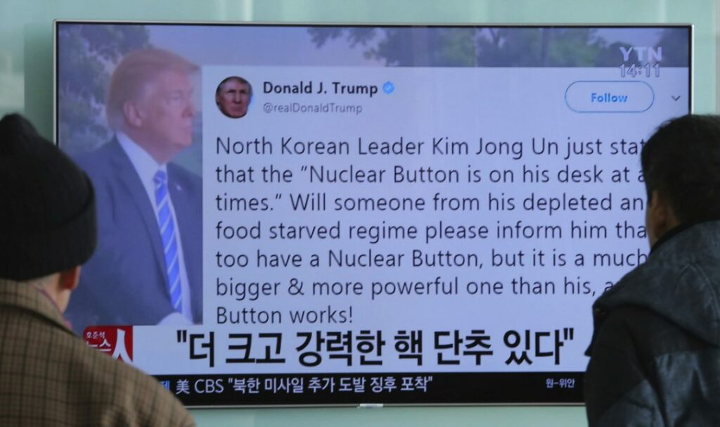 "People watch a TV news program showing the Twitter post of U.S. President Donald Trump while reporting North Korea's nuclear issue at Seoul Railway Station in South Korea on Wednesday. Trump boasted that he has a bigger and more powerful ""nuclear button"" than North Korean leader Kim Jong Un does, but the president doesn't actually have a physical button. The letters on the screen read: ""More powerful nuclear button.""  (AHN YOUNG-JOON / AP)"
