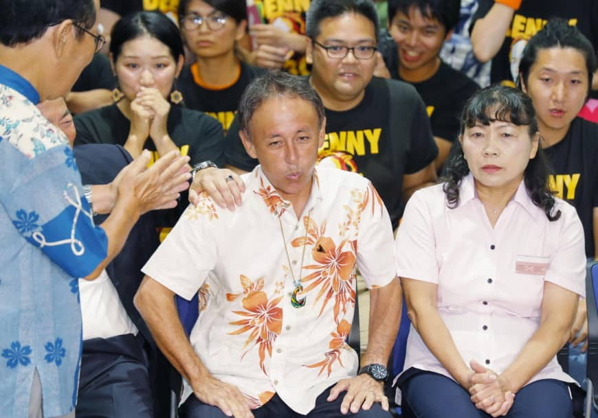 Denny Tamaki, the winner of the Okinawa gubernatorial race, watches the results on TV on Sunday in Naha.