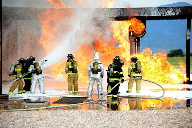 Firefighters at Peterson Air Force Base conduct live training with AFFF. Notice the grassy area just beyond the foam. July 21, 2014. - U.S. Air Force photo/Michael Golembesky