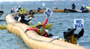 Protesters on canoes display placard as construction workers dumped a truckload of sediment on the ground and bulldozed it into the sea at Henoko on Okinawa's east coast to build a runway for a Marine Corps base, Friday, Dec. 14, 2018. Japan's central government started main reclamation work Friday at a disputed U.S. military base relocation site on the southern island of Okinawa despite fierce local opposition. (Koji Harada/Kyodo News via AP)