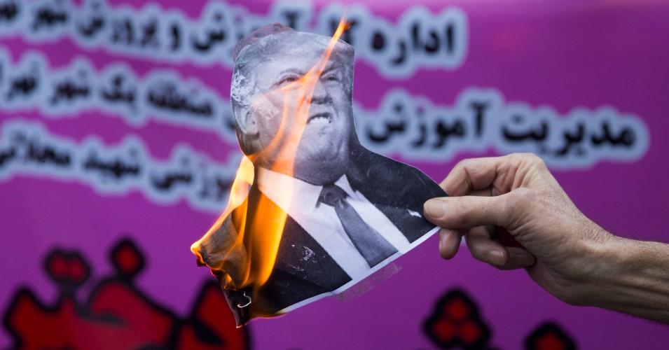 En la antaŭa tago de renovigitaj sankcioj de Vaŝingtono, irana protestanto tenas brulan foton de prezidanto Donald Trump ekster la antaŭa usona ambasado en la irana ĉefurbo Teherano en novembro 4, 2018. (Foto: Majid Saeedi / Getty Images)