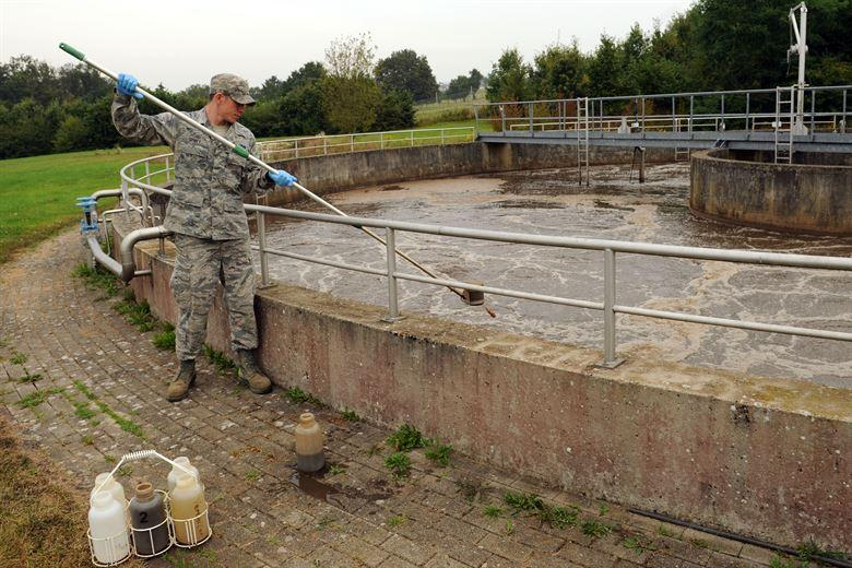 SPANGDAHLEM AIR BASE, Germany Sept. 5, 2012 –Senior Airman David Spivey, 52nd Civil Engineer Squadron water and fuels system maintenance technician, takes a sample of wastewater from a tank during a daily sample inspection at the wastewater treatment facility here. Samples are taken daily from every stage of the treatment process to ensure they meet German environmental standards. The facility processes wastewater from the base to remove any hazardous chemicals it may contain before it is released back into the environment. (U.S. Air Force photo by Senior Airman Christopher Toon/Released)