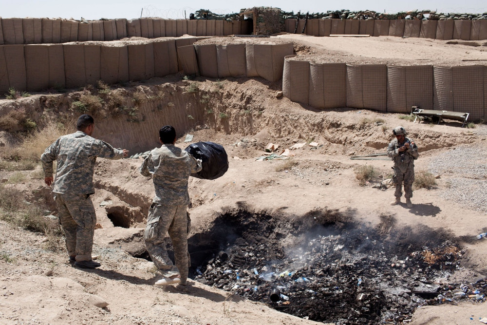 Two interpreters for Bravo troop dump their trash in the base's burn pit in the Zhari District of Kandahar Province, April 2012. Photo: Sebastian Meyer/Corbis via Getty Images