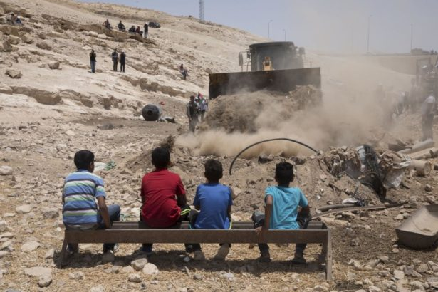 Children watch an Israeli army bulldozer preparing the ground for the demolition of the Palestinian Bedouin village of Khan al-Amar, in the occupied West Bank on July 4, 2018. (Activestills/Oren Ziv)