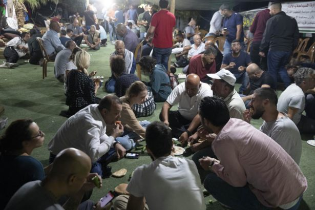 Palestinian and international activists share a meal as they prepare to spend the night in the village's school on September 13, 2018. (Activestills/Oren Ziv)