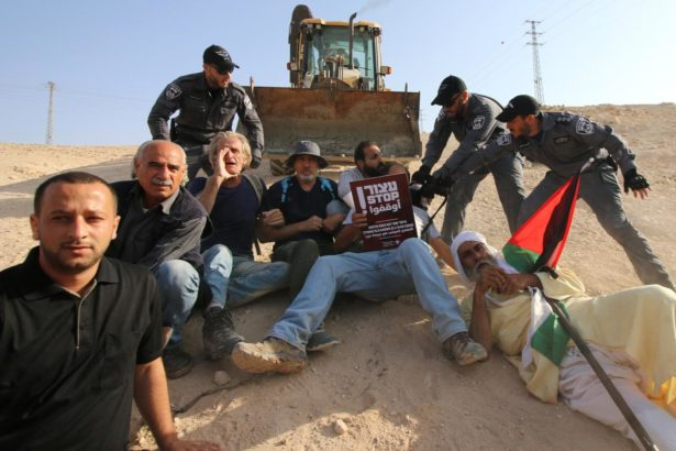 Activists protest in front of an Israeli bulldozer which is escorted by Israeli forces to conduct infrastructure work next to Khan al-Amar on October 15, 2018. (Activestills/Ahmad Al-Bazz)