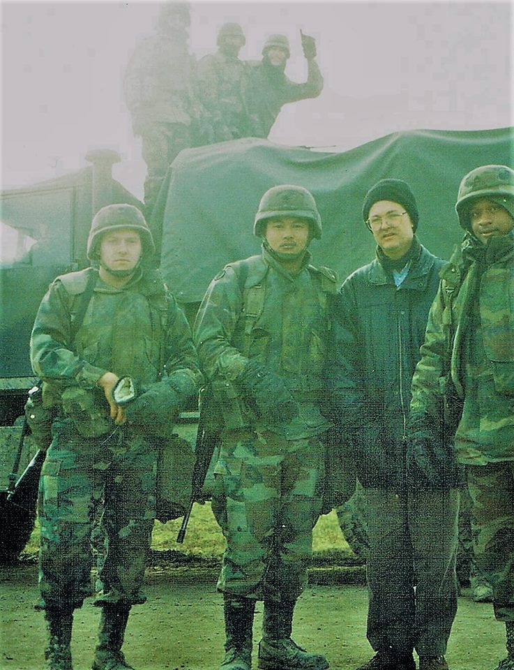"""Pat Elder with U.S. troops in Croatia in 1996. A soldier in the rear shouts """"USA Number 1!"""""""