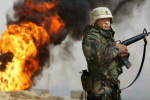 Un soldado estadounidense hace guardia en marzo de 2003 junto a un pozo petrolero en los campos petroleros de Rumayla incendiados al retirarse las tropas iraquíes. (Foto de Mario Tama / Getty Images)