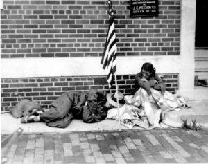 Un veterano de guerra duerme en la acera mientras su esposa se sienta envuelta en mantas en Washington DC el 29 de julio de 1932. Foto | AP