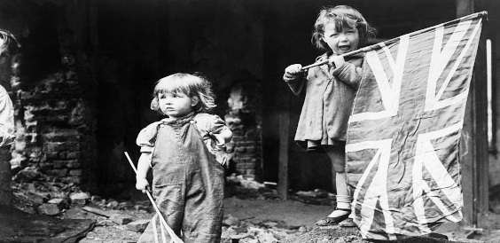 Two small girls waving their flags in the rubble of Battersea.