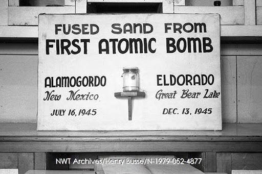 "A sign with a jar of ""fused sand from first atomic bomb; Alamogordo, New Mexico, July 16, 1945; Eldorado, Great Bear Lake, December 13, 1945"" on display in Port Radium, no date., courtesy NWT Archives/Henry Busse fonds/N-1979-052: 4877."