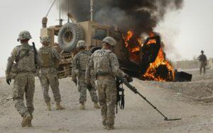 Trupoj de la usona armeo skanis la areon ĉirkaŭ brula blendita veturilo, kiu batis improvizan eksplodan aparaton proksime de Kandaharo, Afganujo, en 2010.