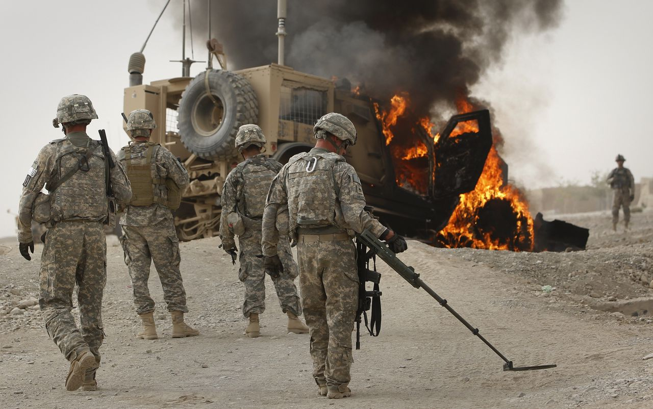 Las tropas del ejército de EE. UU. Escanearon el área alrededor de un vehículo blindado en llamas que golpeó un dispositivo explosivo improvisado cerca de Kandahar, Afganistán, en 2010.