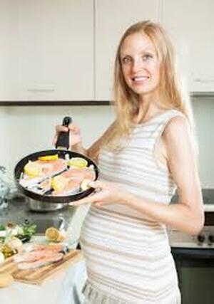 امرأة حامل تطبخ السمك