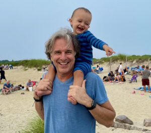 John Miksad on the beach with 15 month old grandson Oliver