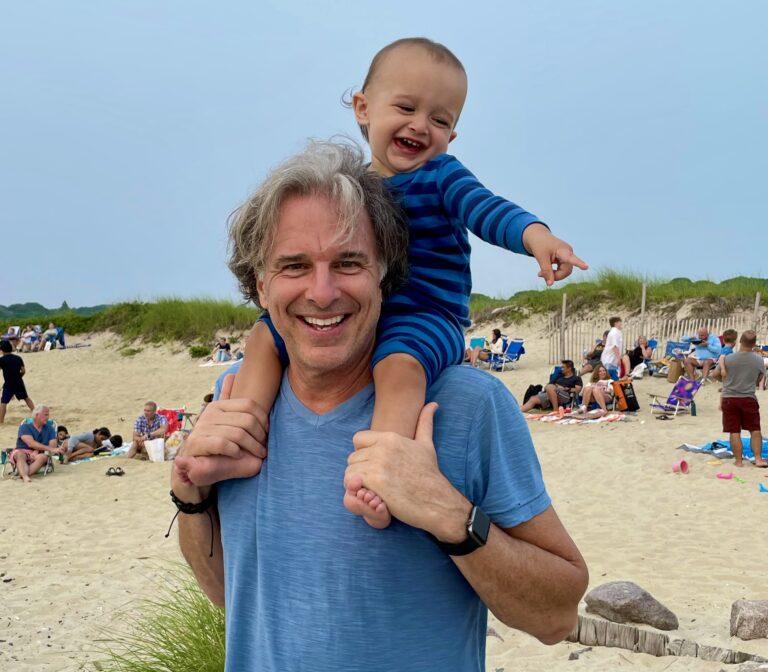John Miksad sur la strando kun 15-monata nepo Oliver